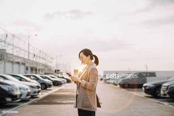 Smart businesswoman reading emails on smartphone in parking lot in early morning