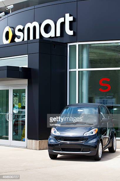 smart car in front of dealership - smart car stock photos and pictures