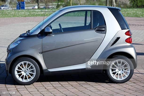 smart car sideview in public parking area - mercedes benz stock photos and pictures