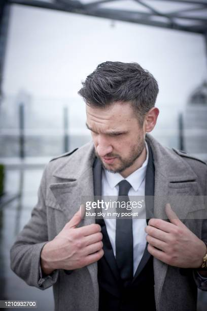 a smart casual business adjusting his coat in the pouring rain. - handsome muscle men stock pictures, royalty-free photos & images