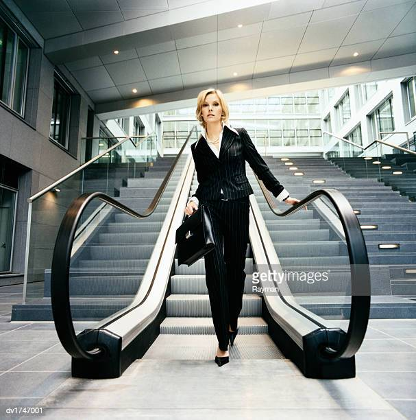 smart confident businesswoman carrying a briefcase descends an escalator - pinstripe stock pictures, royalty-free photos & images