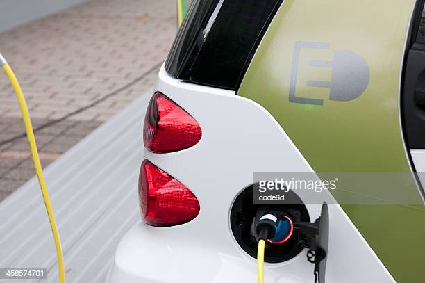 smart electric drive fortwo car charging - daimler ag stock photos and pictures