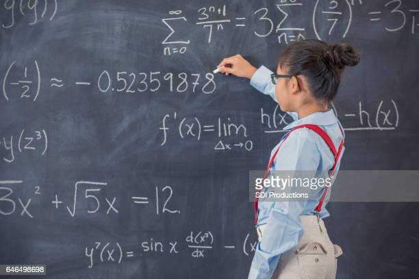 Smart elementary age girl works on math problem