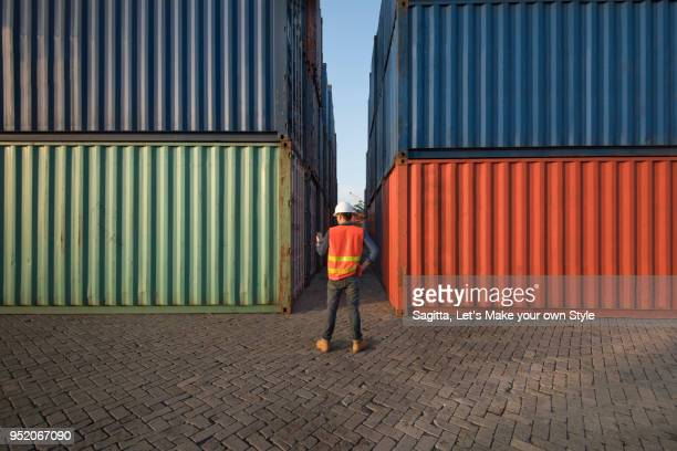 smart engineer foreman looking on his smartphone to check data and control loading containers box from cargo freight ship for import export. business and logistic concept - shipyard stock pictures, royalty-free photos & images