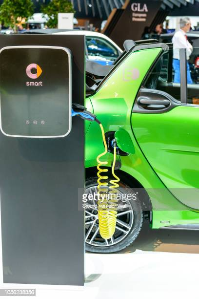 Smart fortwo cabrio electric drive compact convertilbe city car plugged into an electric vehicle charging station on display at Brussels Expo on...