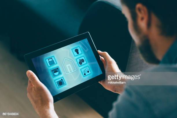 smart home automation in living room with man using digital tablet and mobile app - home icon stock photos and pictures