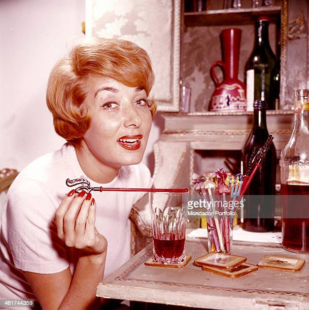 Smart Italian actress Lauretta Masiero glances seductive at the camera with a cocktail decorations in her fingers on the table in front of her straws...