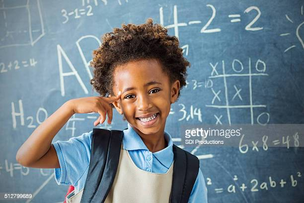 Smart kindergarten private school student pointing at head confidently