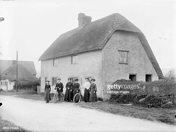 Smart looking group of people standing outside a thatched cottage in the village of Uffington, Oxfordshire, 1916. Two of the group are holding their...