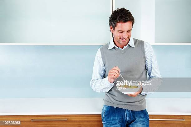 Smart man enjoying a bowl of healthy cereals at home