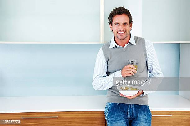 Elegante hombre disfruta de saludables cereales en su hogar
