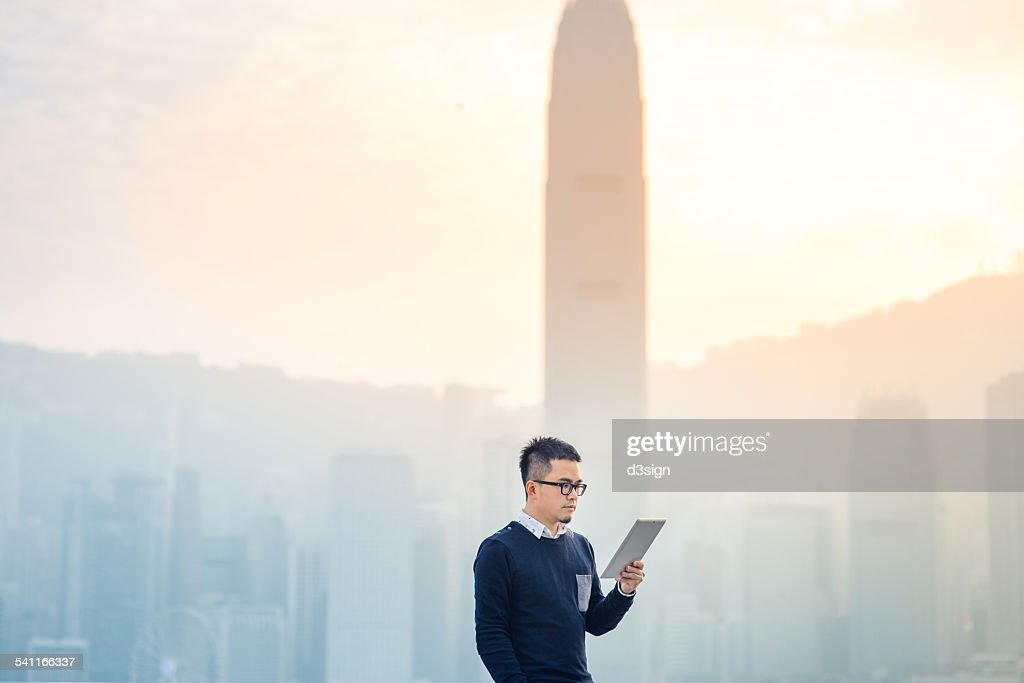 Smart man using digital tablet in urban city : Stock Photo