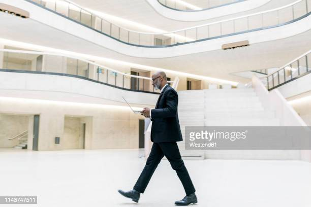 smart mature businessman using laptop while walking through foyer - black suit stock pictures, royalty-free photos & images