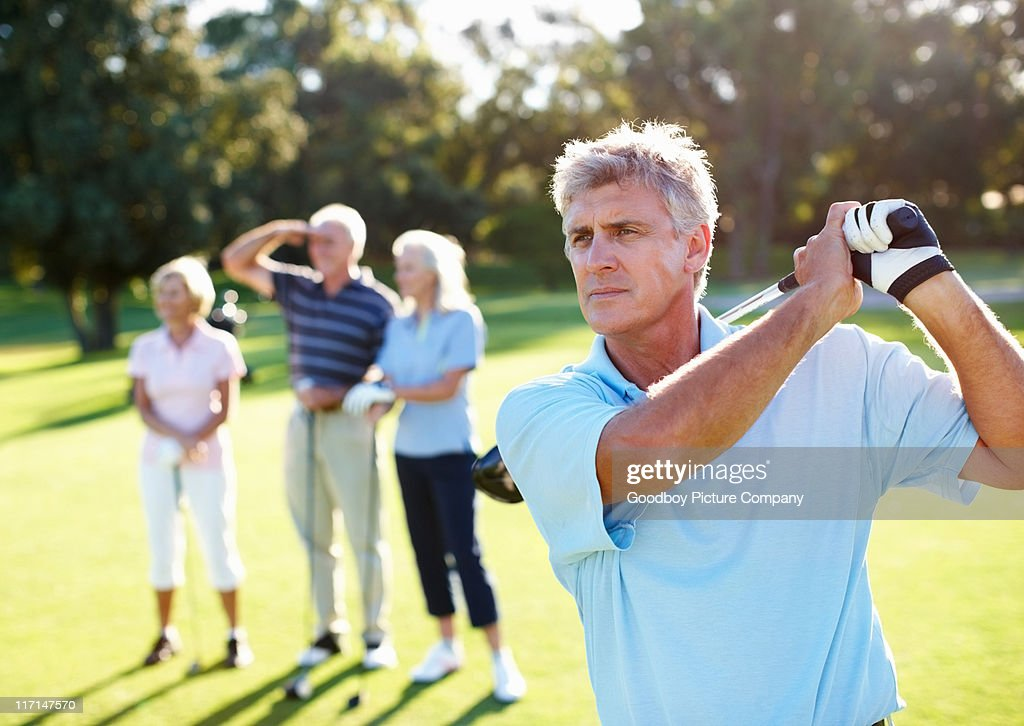 Smart, mature golfer swinging : Stock Photo