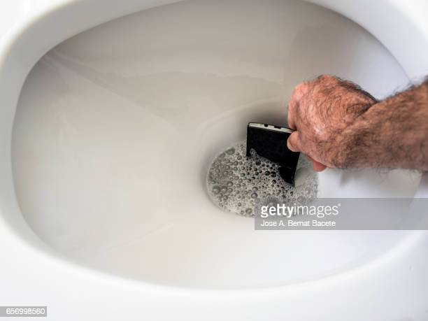 Smart mobile phone dropped in toilet and the hand of a man  grab it