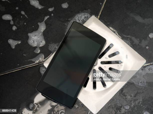 smart mobile phone dropped on the floor of a shower next to the drain with water - mojado stock pictures, royalty-free photos & images