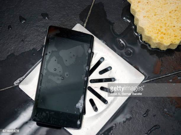 Smart mobile phone dropped on the floor of a shower next to the drain with water