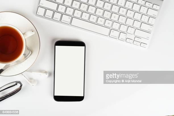 Smart Phone Against White Background With Blank White Screen, Computer Keyboard Copy Space