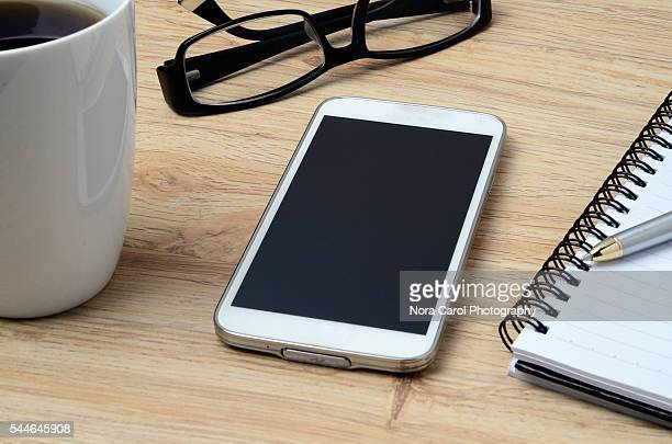 Smart phone, coffee, spectacles and notepad with pen
