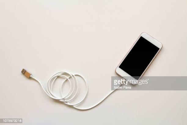 smart phone connected to usb cable - cavo d'acciaio foto e immagini stock