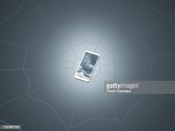 smart phone hanging on a spider web - conspiracy stock pictures, royalty-free photos & images