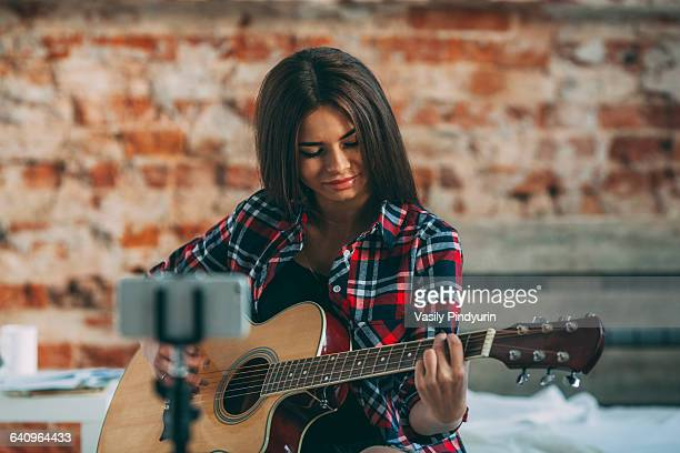 Smart phone in monopod with woman playing guitar at home