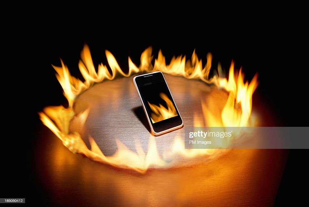 Smart phone in ring of fire : Stock Photo