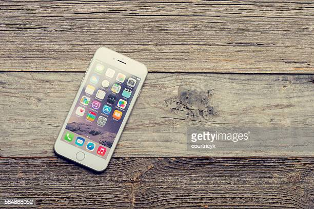 Smart phone on a wood table or surface.