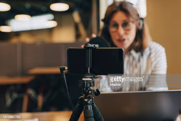 smart phone on tripod filming businesswoman with laptop in office - filming stock pictures, royalty-free photos & images