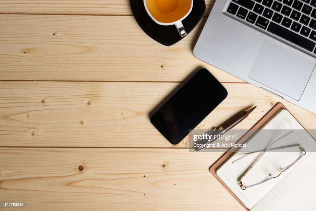 Smart phone on wooden office table top view shot with