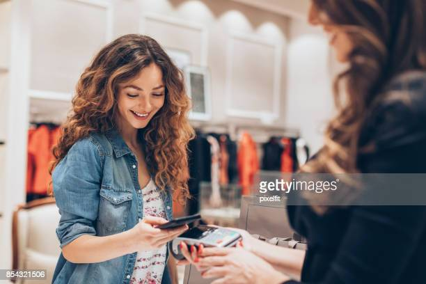 smart phone payment in a fashion retail - shopping stock pictures, royalty-free photos & images