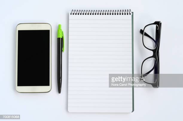Smart phone, pen, eyeglasses and notepad on white background