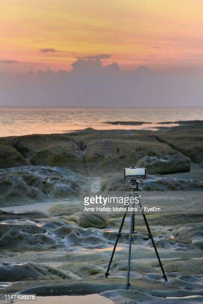 smart phone photographing sea on tripod at beach against sky during sunset - tripod stock pictures, royalty-free photos & images
