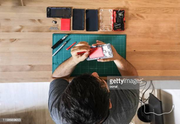 smart phone repairing man with screwdriver - electronics industry stock pictures, royalty-free photos & images