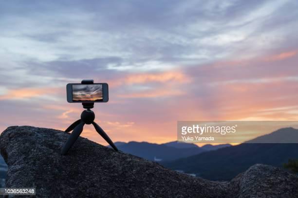 smart phone set on mini-tripod against twilight scenic view - 三脚 ストックフォトと画像