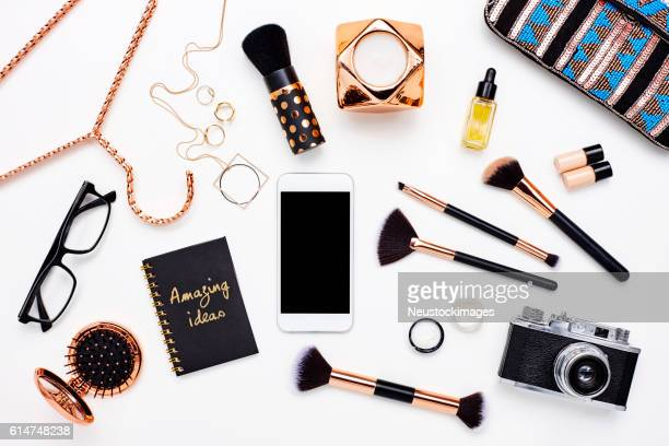 Smart phone surrounded with beauty products on white background