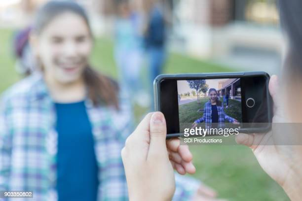 Smart phone taking photo of teen girl outside high school