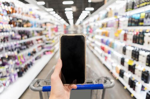 Smart phone with blank screen held up in supermarket - gettyimageskorea