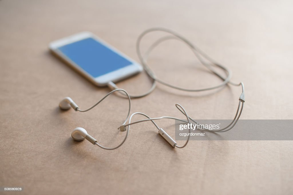 Smart phone with headphones on a brown background : Stock Photo