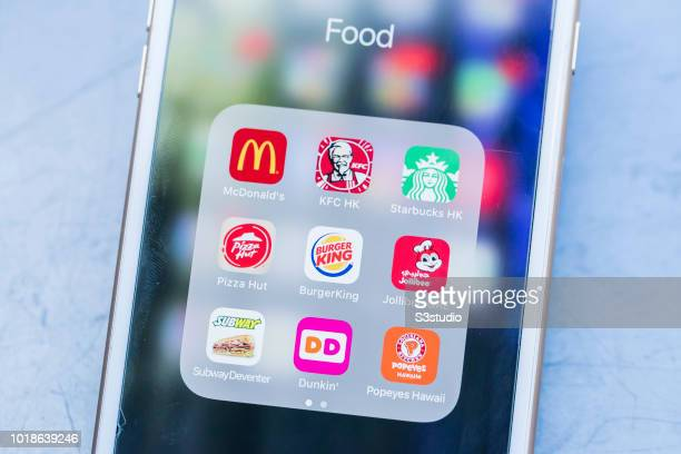 A smart phone with the icons for the fast food apps from McDonald's KFC Starbucks Pizza Hut Burger King Jollibee SUBWAY Dunkin' Donuts and Popeyes...