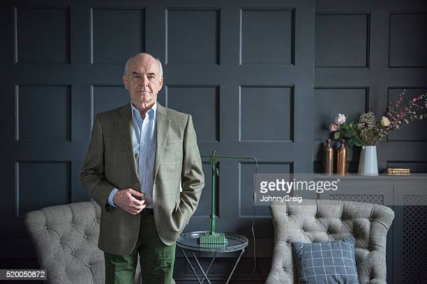 smart senior man in grey wood panelled living room - high society stock pictures, royalty-free photos & images