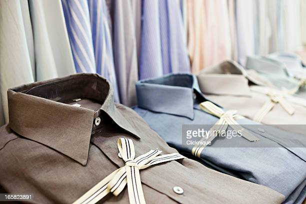 smart shirts tied with striped ribbon in exclusive menswear store - men fashion stock photos and pictures