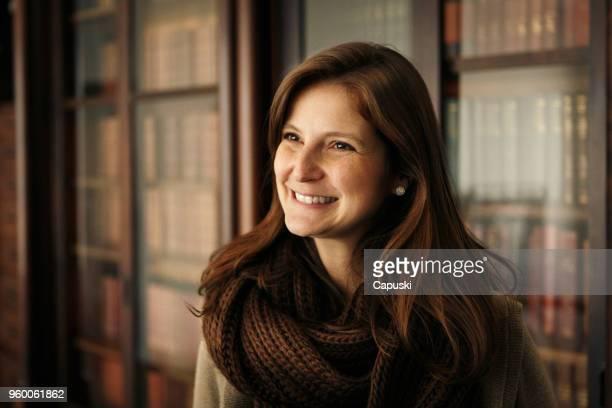 retrato de mulher sorridente inteligente com prateleiras de livros no fundo - advogado - fotografias e filmes do acervo