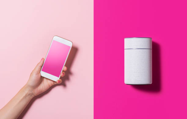 smart speaker and smart phone - human hand stock pictures, royalty-free photos & images