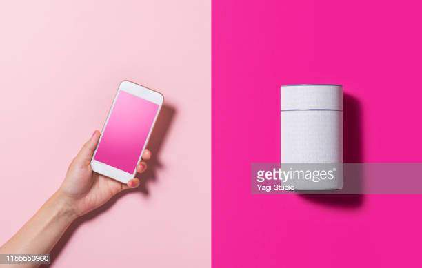 smart speaker and smart phone - telephone stock pictures, royalty-free photos & images