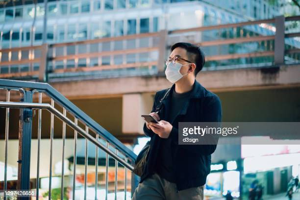 smart young asian businessman with protective face mask using smartphone while commuting in the city after work, against corporate skyscrapers in financial district in the evening. business on the go - hong kong stock pictures, royalty-free photos & images