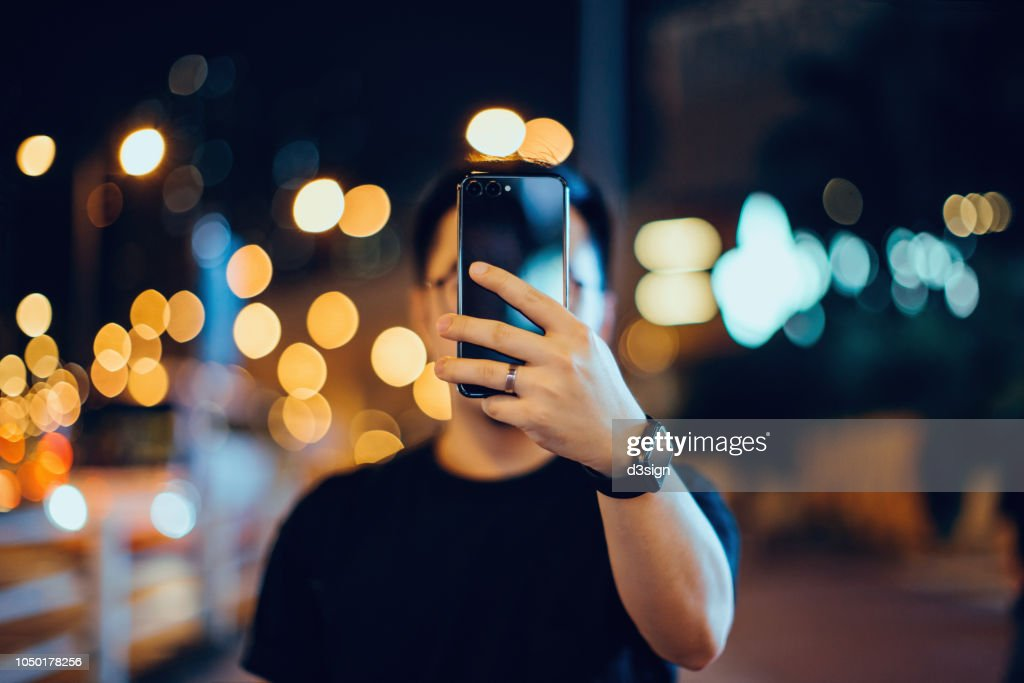 Smart young Asian man taking pictures with smartphone in city street, against illuminated city street light and city traffic : Stock Photo