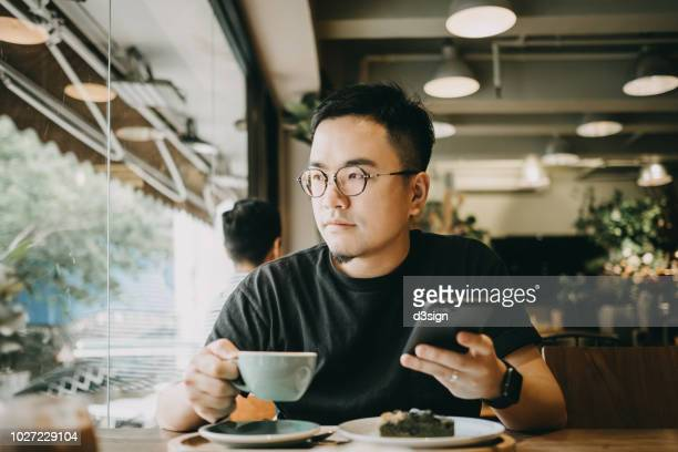 Smart young Asian man using smartphone and having coffee in cafe