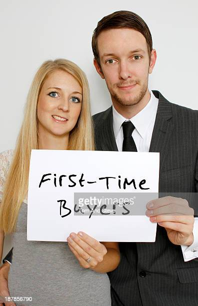 A smart young couple holding a sign