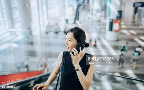 Smart young lady talking on smartphone on escalators